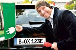 Andre Richter von www.kennzeichenbox.de an einer Elektrotankstelle samt Auto mit E-Schild